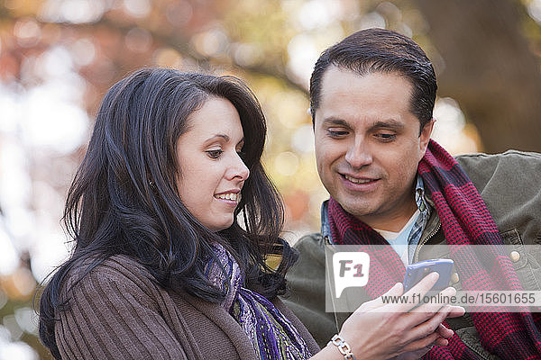 Couple text messaging on a mobile phone