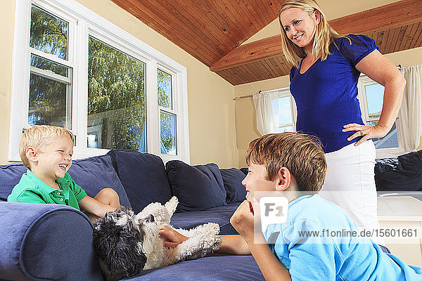 Boys with hearing impairments playing with pets on their couch