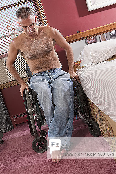 Man with spinal cord injury getting out of his bed and into his wheelchair
