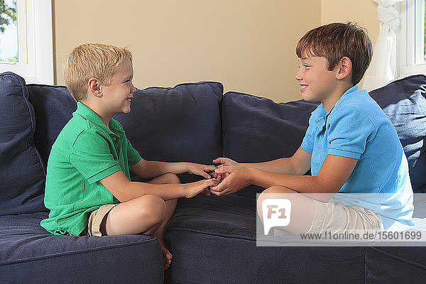 Boys with hearing impairments playing on their couch