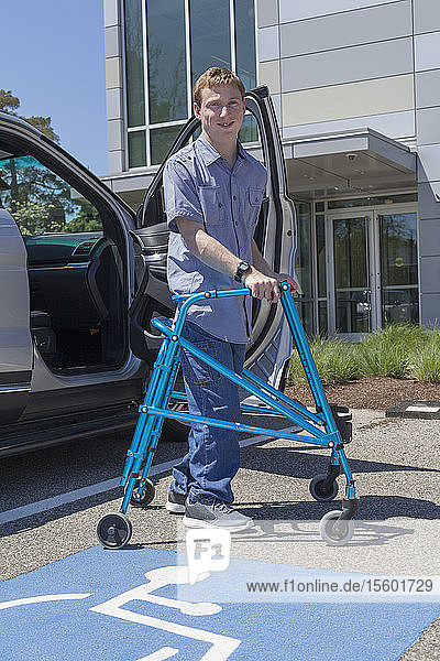 Young man with Cerebral Palsy using his walker to exit a car