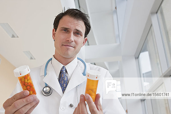 Doctor holding pill bottles