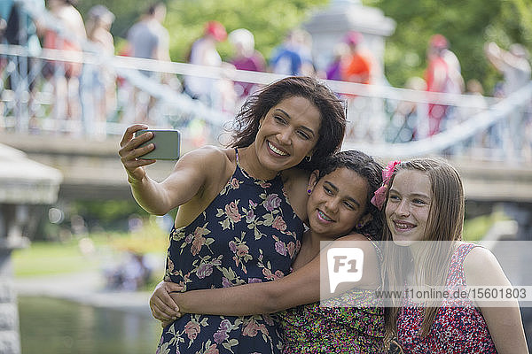 Happy Hispanic mother with two teen daughters taking selfie with mobile phone in park
