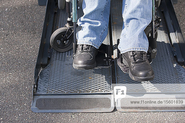 Legs of a man with spinal cord injury in a wheelchair on accessible van ramp