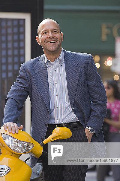Hispanic man smiling near a motor scooter