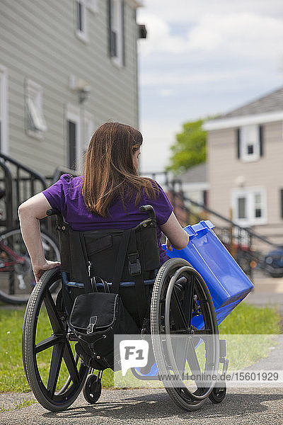 Woman with Spina Bifida in a wheelchair picking up a recycling bin at the street