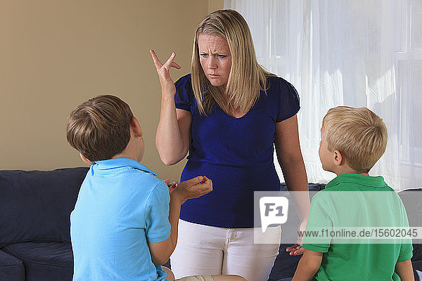 Mother and sons with hearing impairments signing 'why did you do that' in American sign language