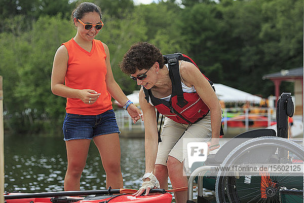 Instructor helping a woman with a Spinal Cord Injury with using a kayak
