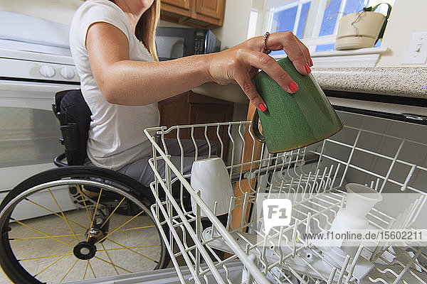 Woman with spinal cord injury in her accessible kitchen putting a cup in dishwasher