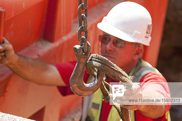 Construction worker placing lifting strap on hook