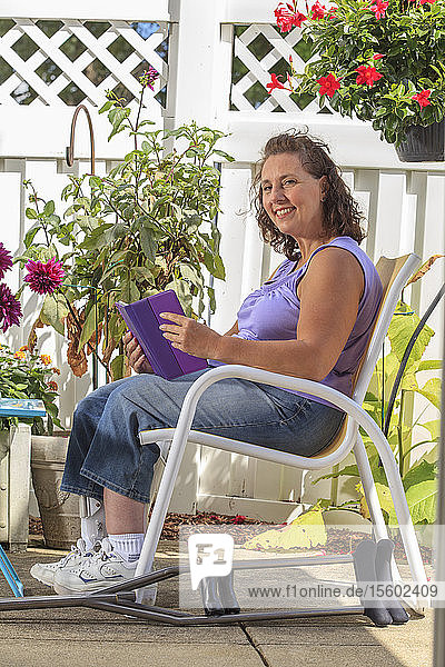 Woman with Spina Bifida on patio working on tablet while on patio