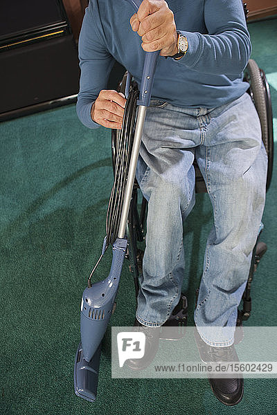Man with spinal cord injury in a wheelchair rewinding power cord on vacuum cleaner