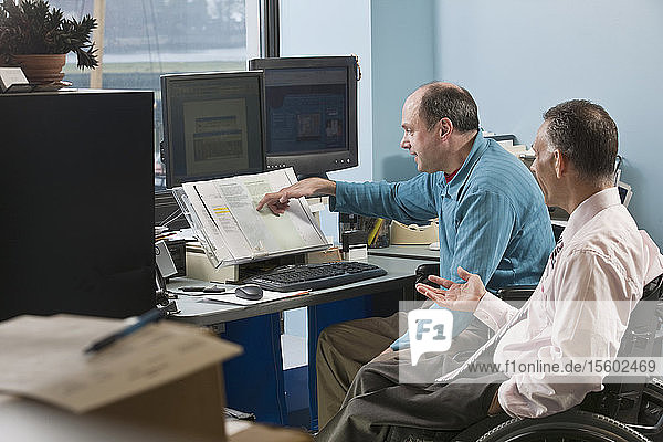 Two businessmen in an office  one with Friedreich's Ataxia and another with spinal cord injury