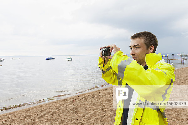 Public works engineer photographing lake where water samples are taken