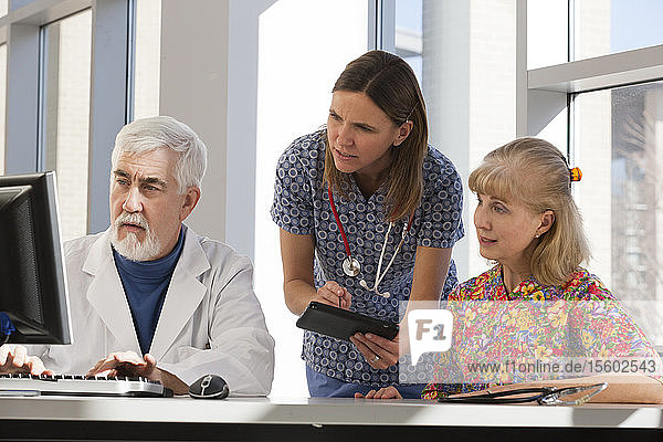 Two nurses and a doctor working on computer and tablet. Doctor has Muscular Dystrophy