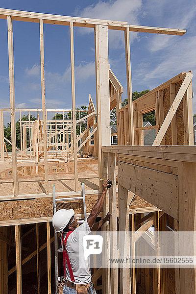 Hispanic carpenter taking a measurement of house framing