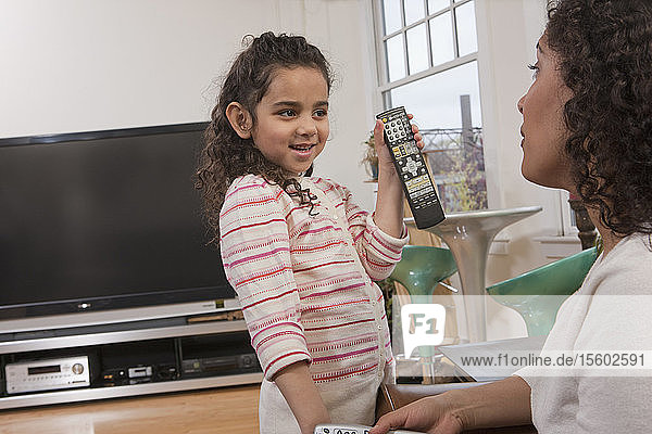 Hispanic girl asking mother how to use the remote control