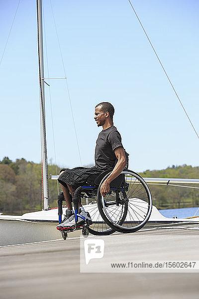 Man in a wheelchair who had Spinal Meningitis at a sailing dock
