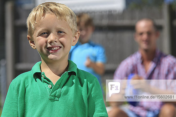 Happy boy with father and brother with hearing impairments playing in backyard