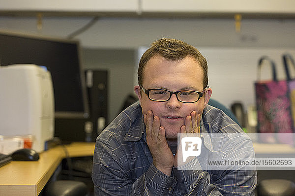 Portrait of hospital aid worker with Down Syndrome sitting at his desk