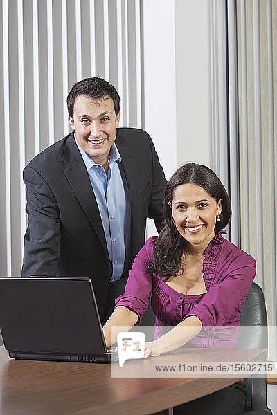 Portrait of businessman and businesswoman at computer