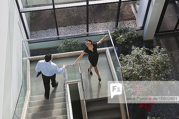 Business couple joyfully walking down stairs of office building