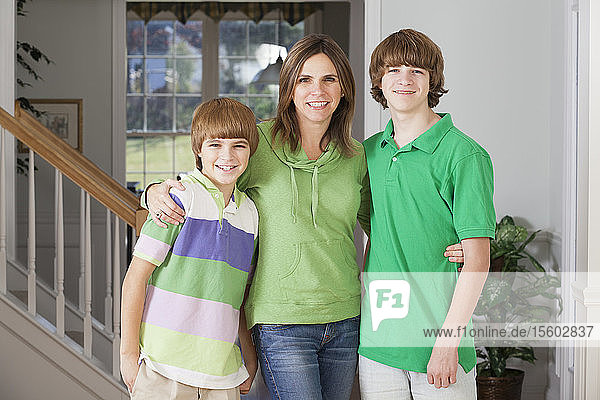 Portrait of a woman standing with their two sons
