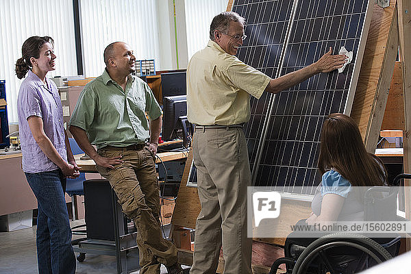 Engineering students watching professor cleaning photovoltaic panel to demonstrate improvement in efficiency
