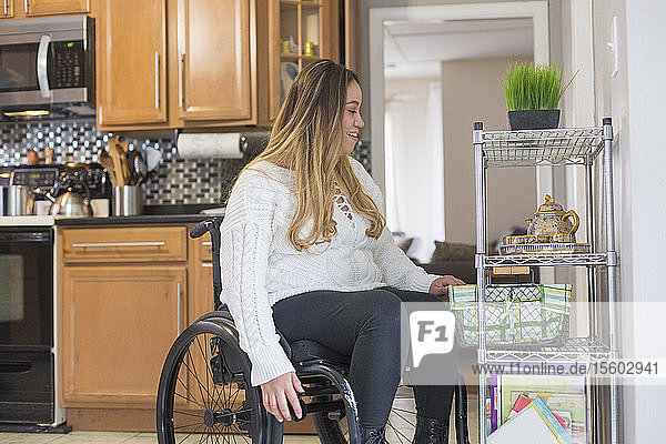 Woman with Spinal Cord Injury arranging things in her kitchen