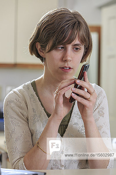 Blind woman using assistive technology to listen to texts on her cell phone