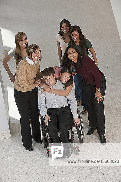 Teacher with spinal cord injury in a wheelchair with students and their mothers