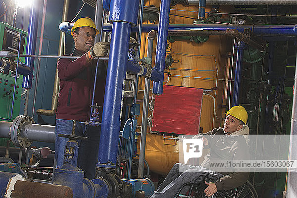 Power plant engineers one with spinal cord injury inspecting demineralization pipes