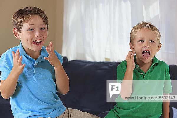 Boys with hearing impairments signing in American sign language on their couch