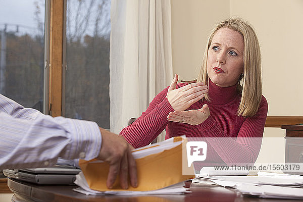 Woman signing the word 'Mortgage' in American Sign Language while communicating with a man