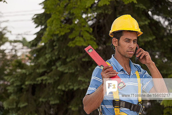 Carpenter holding a level and talking on a mobile phone