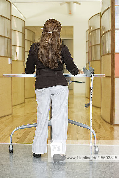 Rear view of a young woman standing by table with cane