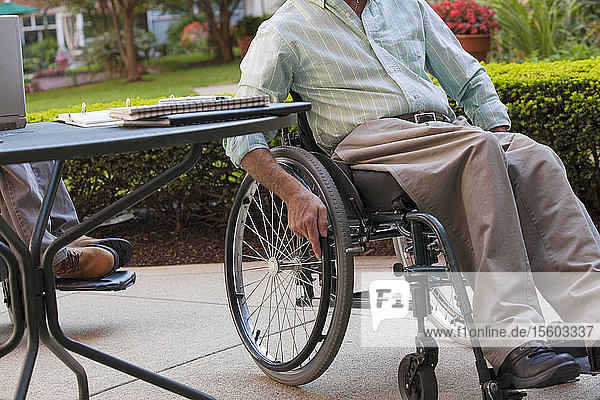 Businessmen with spinal cord injury at a café
