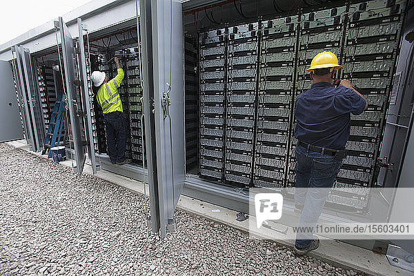 Engineers connecting energy storage batteries for back up power to an electric power plant