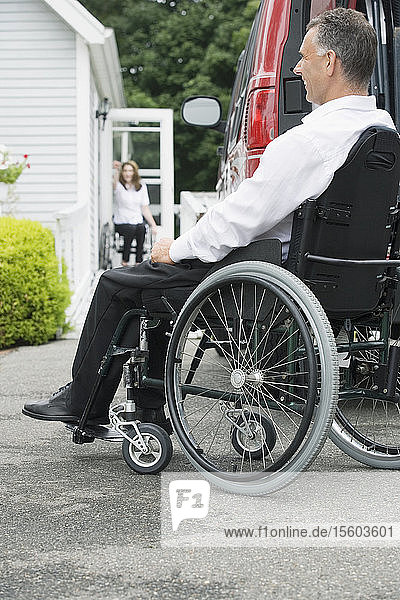 Side profile of a mid adult man with a Spinal Cord Injury and his wifsitting in a wheelchair and smiling
