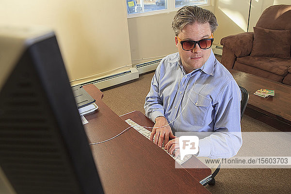 Man with congenital blindness using assistive technology at his computer to listen
