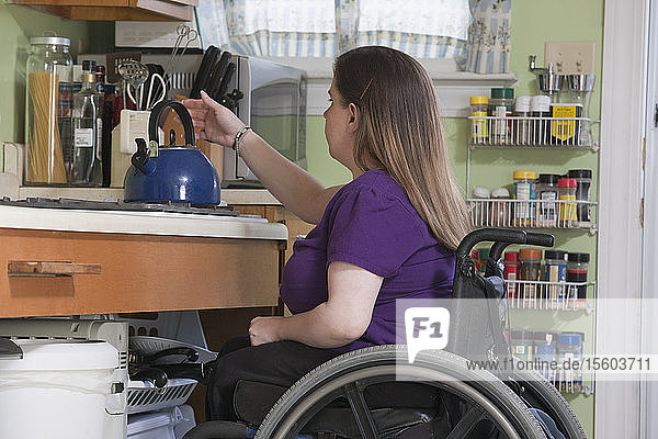 Woman with Spina Bifida in a wheelchair positioning a kettle in the accessible kitchen