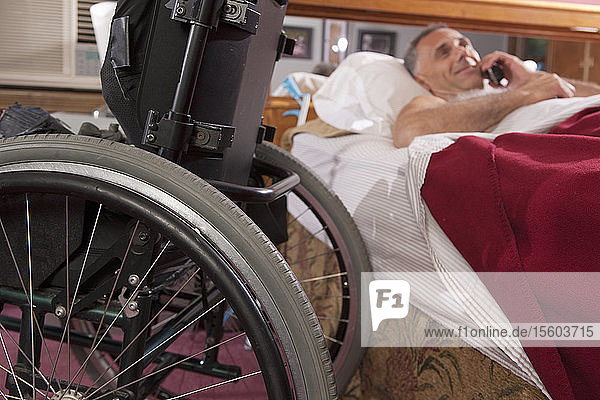 Man with spinal cord injury lying on the bed and talking on a mobile phone