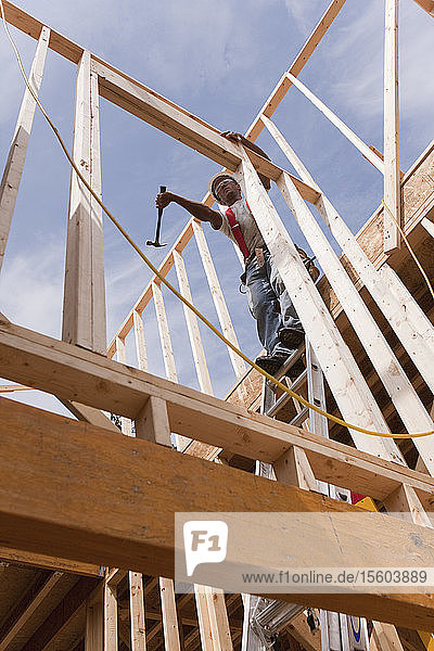 Carpenter using a hammer on the wall frame on the second floor of a house under construction