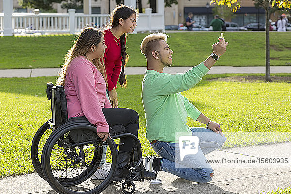 Three friends taking selfie  one with a Spinal Cord Injury