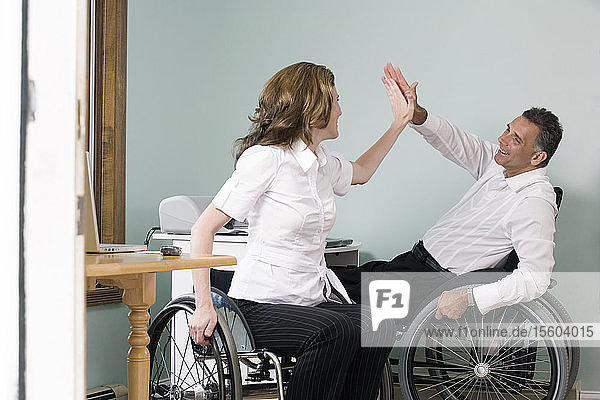 Mature man and a mid adult woman sitting in wheelchairs and giving high-five to each other with a Spinal Cord Injury