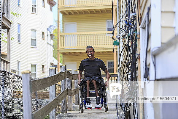 Man in a wheelchair who had Spinal Meningitis on a ramp at his apartment building