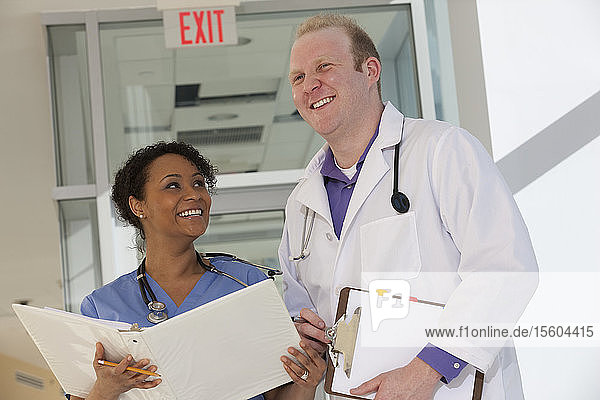Male doctor discussing a medical report with a female nurse