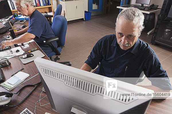 Two engineers on computers starting up the water treatment plant in program for supervisory control and data acquisition