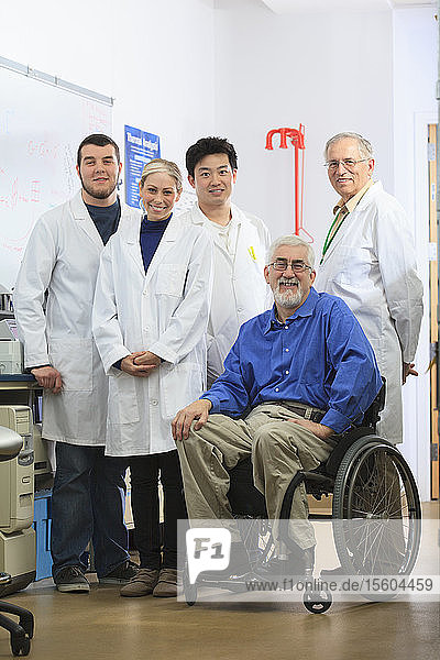 Engineering professors one with muscular dystrophy and students in chemical analysis laboratory