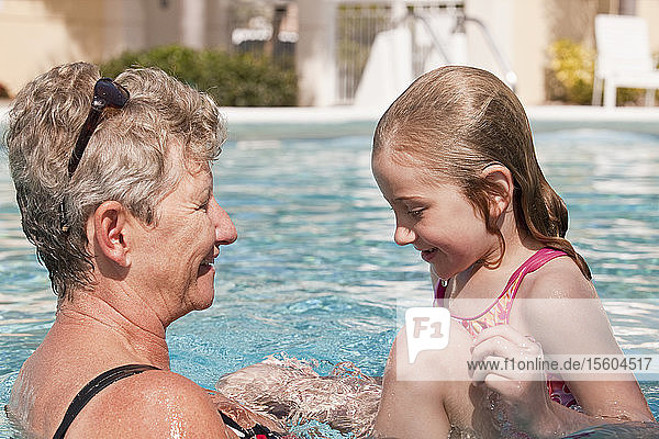 Woman and her granddaughter enjoying in a swimming pool